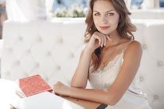 Schönes Studentenmädchen, das für die Prüfungen sitzen an einem Tabellenfreien in einem Sommercafé sich vorbereitet lizenzfreie stockfotografie