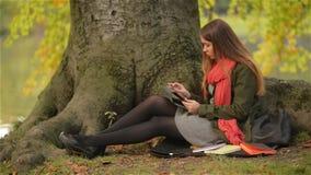 Schönes Studentenmädchen, das Sitzen der Tablette im Freien auf Baum nahe See verwendet stock footage