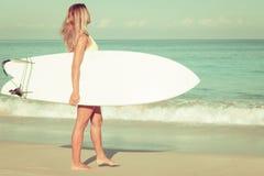 Schönes Surfer-Mädchen, das auf den Strand geht Stockfoto