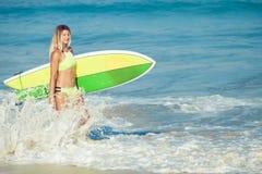 Schönes Surfer-Mädchen, das auf den Strand geht Lizenzfreies Stockfoto
