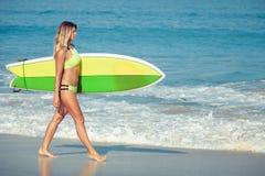 Schönes Surfer-Mädchen, das auf den Strand geht Stockfotografie