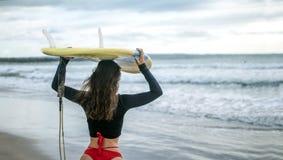 Schönes Surfermädchen, das unten zum Strand für tragendes Surfbrett der Sonnenuntergangbrandungs-Sitzung auf Kopf, Kopienraum, fr stockbild