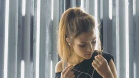 Schönes Tanzen der jungen Frau in einem Nachtklub, hörend Musik durch Kopfhörer Schneller Energietanz stock footage