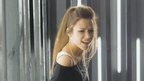 Schönes Tanzen der jungen Frau in einem Nachtklub, hörend Musik durch Kopfhörer Singt ein Lied vor der Kamera stock video