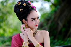 Schönes thailändisches Mädchen im Trachtenkleidkostüm als thailändischem Tempel Stockfoto