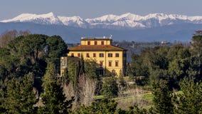 Schönes toskanisches Herrenhaus mit schneebedeckten Bergen im Hintergrund, Pontedera, Pisa, Toskana, Italien lizenzfreie stockfotos