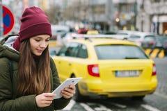 Schönes touristisches Mädchen mit einer Tablette auf einer Straße in Prag ruft ein Taxi oder betrachtet eine Karte oder verwendet stockbilder