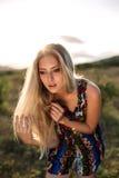 Schönes träumerisches blondes Mädchen mit blauen Augen in einem hellen Türkiskleid, das auf den Steinen liegt Stockbilder