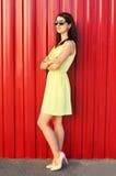 Schönes Tragen der jungen Frau Sonnenbrille und gelbes Kleid über buntem Rot Stockfotos