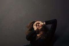 Schönes trauriges Händchenhalten der jungen Frau auf ihrem Gesicht auf einem dunklen Hintergrund Stockfotos