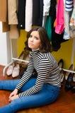 Schönes trauriges junges Mädchen, das unter ihr Kleidung und Schuhe sitzt Lizenzfreies Stockbild