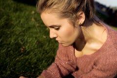 Schönes trauriges Mädchen sitzt auf Sommernatur. Lizenzfreie Stockfotos