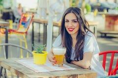 Schönes trinkendes Bier der jungen Frau und Genießen des Sommertages Stockfotos