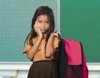 Schönes und exotisches schauendes weibliches Kind in tragender Studententasche der Schuluniform lächelnd vor Klassenzimmertafel i stockfoto