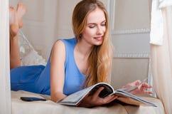 Schönes und junges Mädchen, das auf dem Bett liegt und eine Zeitschrift liest Lizenzfreie Stockbilder