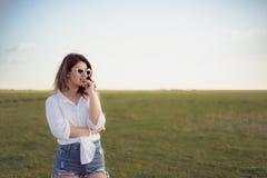 Schönes und Modeporträt von awoman auf grünem Feld Lizenzfreie Stockfotos