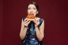 Schönes und modernes Brunettemodellmädchen im blauen Kleid die Pizza essend, lokalisiert am weinartigen Hintergrund, zuhause stockfoto