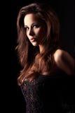 Schönes und reizvolles Brunettemädchen auf Dunkelheit Lizenzfreies Stockbild