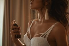 Schönes und verlockendes brunette vorbildliches Mädchen mit perfektem sexy Körper in der modernen Spitzewäsche, die Parfüm auf ih lizenzfreie stockbilder