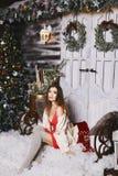 Schönes und vorbildliches Mädchen mit perfektem Körper, im kurzen roten Kleid und in den Strümpfen, sitzt vor den Türen nahe lizenzfreies stockfoto