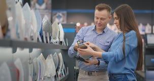 Schönes verheiratetes Paar kauft ein neues Eisen für ihr Haus Halten Sie das Eisen im Speicher, um die Eigenschaften zu studier stock footage