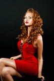 Schönes, verwegenes red-haired Mädchen in einem roten Kleid Stockfotografie