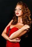 Schönes, verwegenes red-haired Mädchen in einem roten Kleid Lizenzfreie Stockfotos