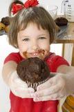 Schönes vier Einjahresmädchen mit Schokoladen-Chip-Muffin stockfotos