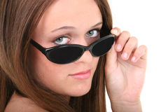 Schönes vierzehn Einjahresmädchen, das über Sonnenbrillen schaut Lizenzfreie Stockfotografie