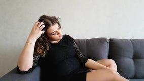 Schönes volles Mädchen, das auf der Couch, trauriges, romantisches Träumen sitzt stock video footage