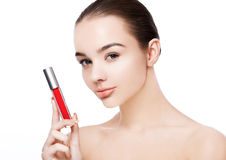 Schönes vorbildliches Mädchen, das flüssigen roten Lippenstift hält Stockfotografie