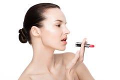 Schönes vorbildliches Mädchen, das Lippenstiftrohrmake-up hält Lizenzfreie Stockfotografie