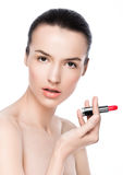 Schönes vorbildliches Mädchen, das Lippenstiftrohrmake-up hält Stockbilder