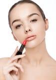 Schönes vorbildliches Mädchen, das Lippenstiftrohrmake-up hält Lizenzfreies Stockfoto