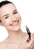 Schönes vorbildliches Mädchen, das Lippenstiftrohrmake-up hält Stockbild