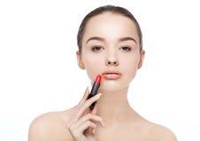 Schönes vorbildliches Mädchen, das Lippenstiftrohrmake-up hält Lizenzfreie Stockbilder