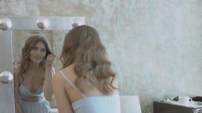 Schönes vorbildliches zutreffendes Pulver zum Gesicht unter Verwendung der Bürste und Stellung vor dem Spiegel stock video footage