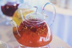 Schönes warmes Bild des transparenten Teekannenkessels mit geschmackvollem grünem schwarzem Tee mit Apfel Lizenzfreie Stockfotografie