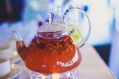 Schönes warmes Bild des transparenten Teekannenkessels mit geschmackvollem grünem schwarzem Tee mit Apfel Stockbilder