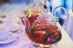 Schönes warmes Bild des transparenten Teekannenkessels mit geschmackvollem grünem schwarzem Tee mit Apfel Lizenzfreie Stockfotos