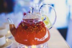 Schönes warmes Bild des transparenten Teekannenkessels mit geschmackvollem grünem schwarzem Tee mit Apfel Stockfoto