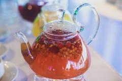 Schönes warmes Bild des transparenten Teekannenkessels mit geschmackvollem grünem schwarzem Tee mit Apfel Stockbild