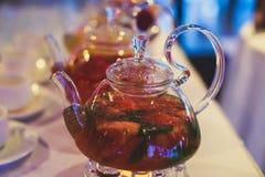 Schönes warmes Bild des transparenten Teekannenkessels mit geschmackvollem grünem schwarzem Tee mit Apfel Lizenzfreies Stockbild