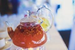 Schönes warmes Bild des transparenten Teekannenkessels mit geschmackvollem grünem schwarzem Tee mit Apfel Stockfotografie