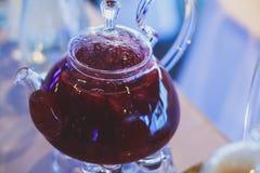 Schönes warmes Bild des transparenten Teekannenkessels mit geschmackvollem grünem schwarzem Tee mit Apfel Lizenzfreies Stockfoto