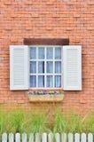 Schönes weißes hölzernes Fenster auf Backsteinmauer Lizenzfreies Stockfoto