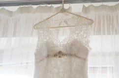 Schönes weißes Hochzeitskleid, das durch Fenster hängt Stockfotografie