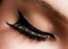 Schönes weibliches Auge mit den extremen langen Wimpern, schwarzes Zwischenlagenmake-up Perfektes Make-up, lange Peitschen Nahauf Lizenzfreies Stockfoto