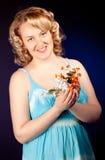Schönes weibliches Baumuster, das blaues Kleid auf dunklem Hintergrund trägt lizenzfreie stockfotografie