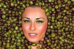 Schönes weibliches Gesicht in der Stachelbeere Stockfoto